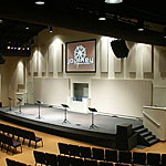 Photo of a stage in a house of worship with acoustic panels installed.