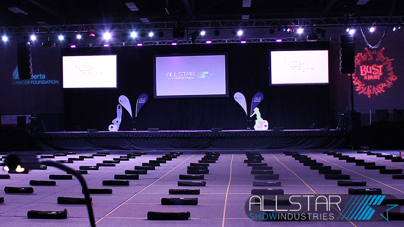 Looking towards the stage with three video screens a truss full of lights and NEXO line arrays.