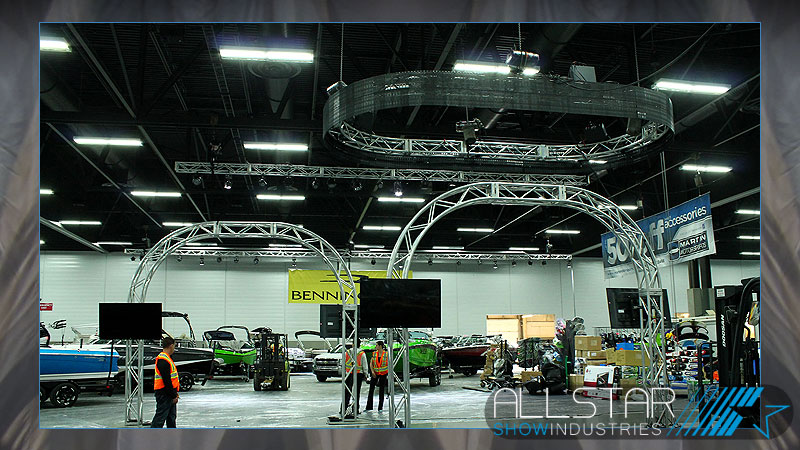 Truss arches with video displays being set-up by Allstar Show Industries in Martin Motor Sports trade show booth.