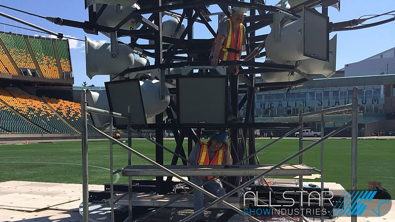 Installers hanging new Community loudspeakers on the new speaker pod at Edmonton's Commonwealty Stadium.